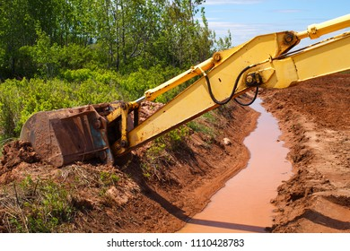 Excavator bucket and hydraulic arm extended over a muddy ditch.