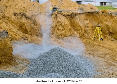 Excavator bucket moving gravel stones for foundation building working on a construction site