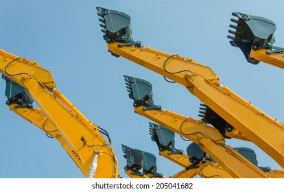 excavator bucket on the end of a yellow hydraulic arm of a digging machine.