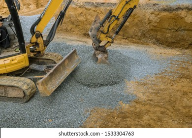 Excavator bucket shovel moving stones of foundation backfilling stone of foundation