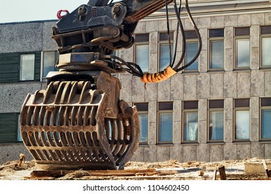 An excavator bucket standing by at a demolition site in the middle of the town of Oulu in the Northern Finland.