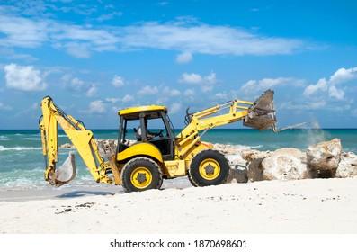 The excavator building wave breaker on Grand Cayman island Seven Mile Beach (Cayman Islands).