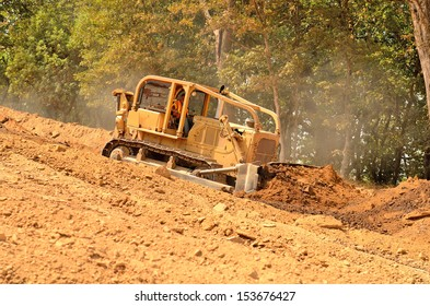 Excavator bulldozer pushes top soil and loose dirt down a hill at a new commercial construction development project