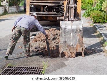 Excavator, bulldozer with workers work a hole repair of pipe water and sewerage on road