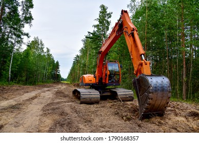 Excavator clearing forest for new development. Orange Backhoe modified for forestry work. Tracked heavy power machinery for forest and peat industry. Logging, road construction in forests - Shutterstock ID 1790168357