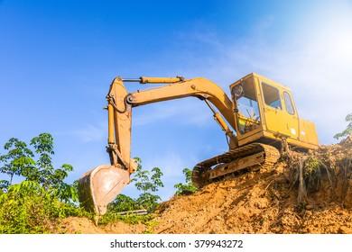 excavator in construction site against blue sky
