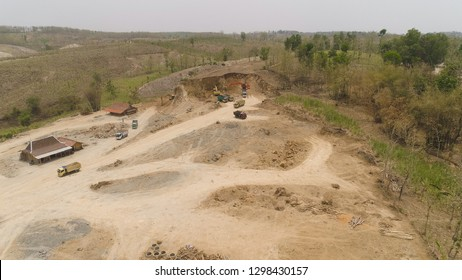 excavator at construction site cuts hill and loads truck with earth. aerial view Heavy machinery prepares the countryside for construction. Excavators are been used in large and small scale