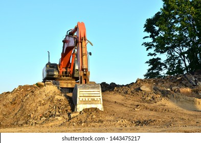 Excavator at a construction site during earthworks and laying of underground pipes. Professional excavation contractor serving, trenching, grading for residential, commercial, and municipal projects