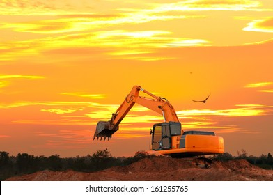 Excavator at construction site with golden sky sunset  in the evening