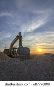 excavator in construction site at stunning sunset.