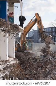 Excavator demolishing derelict building