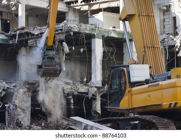 Excavator with demolition grapple demolishing building