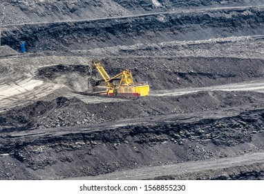 The excavator is developing a coal-based platte. Mining face quarry, mining.