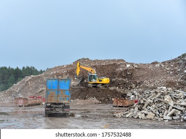 Excavator dig construction waste at landfill. Truck with metal tank and capacitie for storage and transportation of garbage . Disposal and concrete crushing. Salvaging and recycling