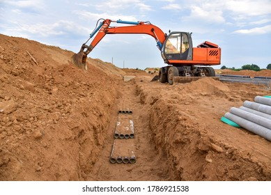 Excavator dig the trenches at a construction site. Trench for laying external sewer pipes. Sewage drainage system for a multi-story building.