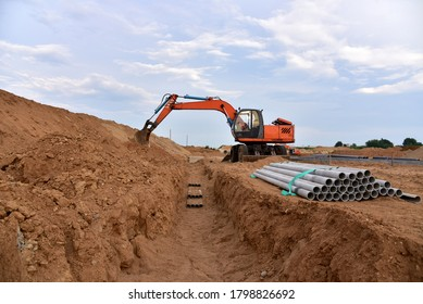 Excavator dig the trenches at a construction site. Trench for laying external sewer pipes. Sewage drainage system for a multi-story building. Civil infrastructure pipe, water lines and sanitary storm