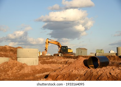 Excavator dig the trenches at a construction site. Trench for laying external sewer pipes. Sewage drainage system for a multi-story building. Digging the pit foundation.