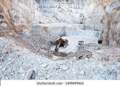 Excavator or digger inside an open cast mining pit for white Carrara marble showing large blocks of stone cut from the mountainside in Tuscany, Italy