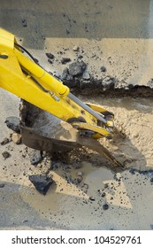 excavator digging a hole, breaking street asphalt, repairing damaged water supply