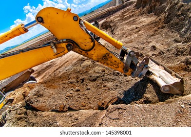 Excavator digging a hole and loading a dumper truck with soil in construction site
