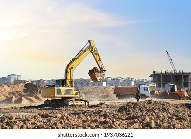 Excavator digging sand and loading into dump truck on construction site. Backhoe digs the ground, foundation for the construction of a new residential building. Tower cranes in action