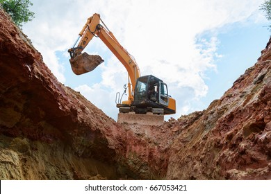 Excavator digging a trench. Work on the construction site.