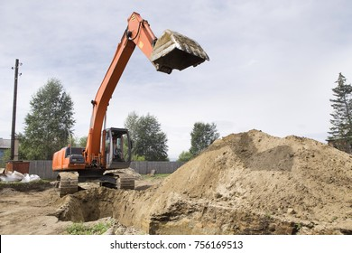 Excavator is digging a trench. Work on the construction site. Digging trenches for laying communications to the building under construction.
