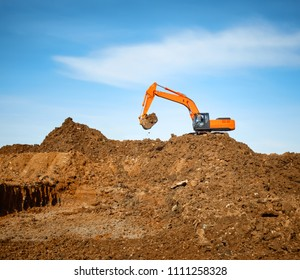 Excavator digs the earth on a background of blue sky