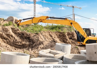 An excavator digs a foundation pit for the construction of a residential building. New residential buildings in the background. Construction production. Excavation