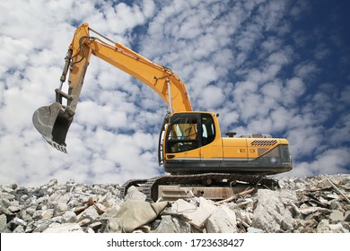 Excavator digs the ground for the foundation and construction. Excavator   working demolition site.Heavy excavator with shovel standing on hill with rocks