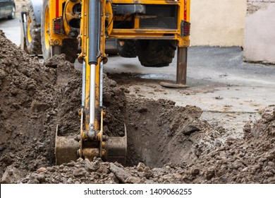 Excavator digs a trench. Repair work in the courtyard of a residential building.