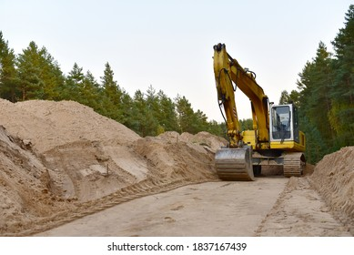 Excavator during construction new road in forest area. Backhoe at groundwork. Earth-moving equipment fort road work, grading, pool excavation, utility trenching.