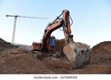 Excavator during earthmoving at construction site. Backhoe digg ground at construction site for the construction of the road and laying sewer pipes district heating. Earth-moving heavy equipment