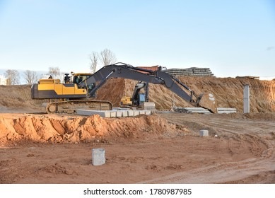 Excavator during excavation at construction site. Backhoe on foundation work in sand pit. Groundworks, site levelling, construction of reinforced ground beams on piled foundations .