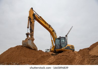 Excavator at earthworks on construction site. Backhoe loader digs a pit for the construction of the foundation. Digging trench for laying sewer pipes drainage in ground. Earth-Moving Heavy Equipment