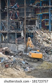 Excavator in front of a big metal construction destroyed