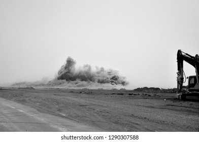 Excavator in front of the blast on the construction site in the Oman