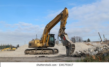 An excavator in front of a pile of  rubble  during an urban redevelopment. In the background two telescopic cranes