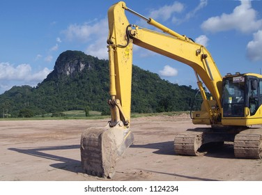 Excavator in front of small, green mountain