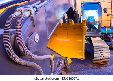Excavator, front view. Large excavator bucket. Construction equipment. Road machinery. Machine for digging holes. Tracked vehicles. Excavator with empty cab.
