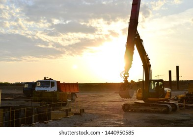 Excavator with grab bucket and telescopic boom for deep digging in the construction of underground structures, lifting materials from deep holes, excavation from the pit. Sunset at a construction site