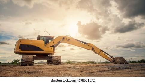 excavator heavy machine construction site on sunset sky background