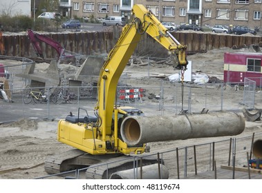 Excavator hoisting a sewer pipe