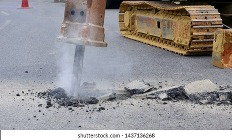 Excavator hydraulic crushing hammer is breaking asphalt road for preparing to install water piping system work, close up and selective focus