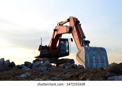 Excavator with a large iron bucket breaks asphalt on a construction site. Demolition work concrete, replacing asphalt, road works. Stone mine in open pit. Loading of stone and rubble - Image