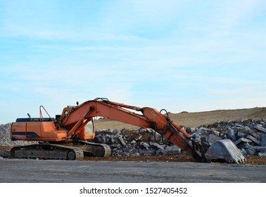 Excavator with a large iron bucket breaks asphalt on a construction site. Demolition work concrete, replacing asphalt, road works. Digging the ground for the foundation and construction of a new build