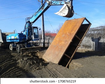 Excavator lifting a trench shoring box. Sewerage system construction