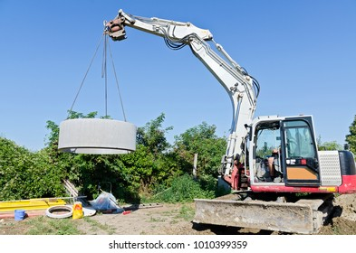 excavator llifting concrete ring of a sink