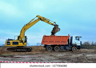 Excavator load the sand to the heavy dump truck on construction site. Excavators and dozers digs the ground for the foundation and construction of a new building. Apartment renovation program