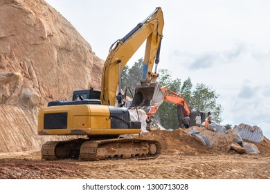 An excavator loader machine and stone jacking machine during earthmoving works at construction site at mountain. Three of workers standing turn back, looking at the excavator and large jackhammer.